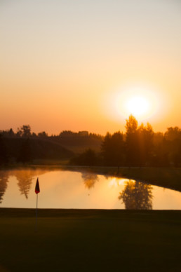 sun setting over water hazard and hole flag at The Links at Spruce Grove