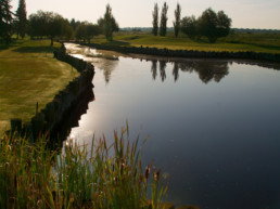 sun setting over water hazard at The Links at Spruce Grove