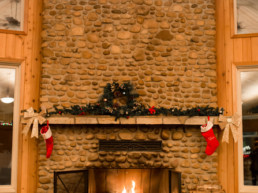 stone fireplace decorated for Christmas inside at The Links at Spruce Grove