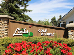 The Links at Spruce Grove sign lined with landscaping and red flowers